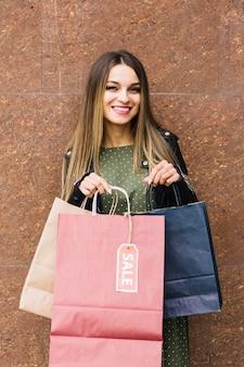 Modieuze jonge vrouw die zich tegen muur bevindt die vele het winkelen zakken houdt