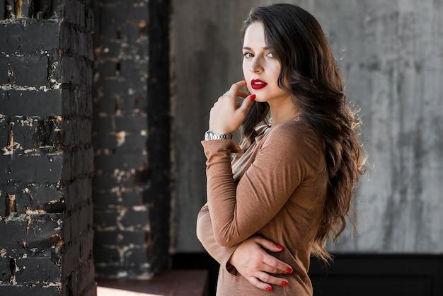 Modieuze jonge vrouw die zich tegen muur bevindt