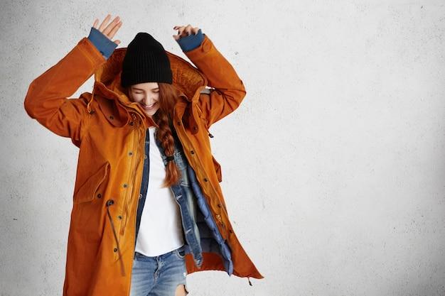 Modieuze jonge vrouw, gekleed in rode winterjas, zwarte hoed en haveloze jeans verhogen handen in de lucht
