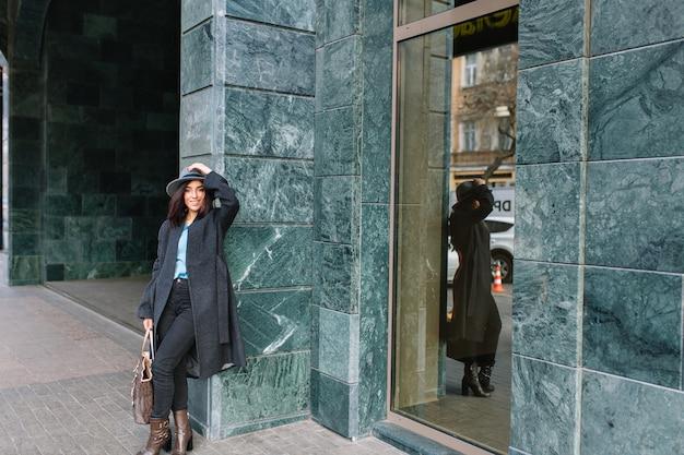 Modieuze jonge vrouw in grijze jas, hoed lopen op straat in het centrum. glimlachen, echte emoties, stijlvolle levensstijl, luxe kleding, elegante uitstraling.