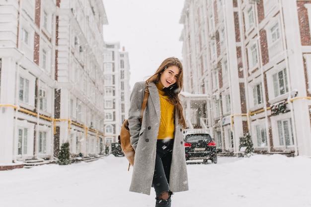 Modieuze jonge vrouw in jas met rugzak lopen op straat in de grote stad in sneeuwt tijd. vrolijke stemming, sneeuwval, wachten op kerstmis, positiviteit uiten, ware emoties.