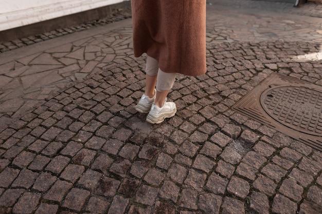 Modieuze jonge vrouw in lange elegante jas in beige broek in lederen stijlvolle jeugd sneakers. trendy meisje in lente casual kleding loopt op stenen weg in de stad. doordeweekse mode. detailopname. achteraanzicht.