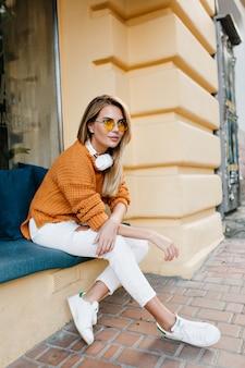 Modieuze jonge vrouw in lederen sneakers rusten na een reis door de stad en op zoek naar camera
