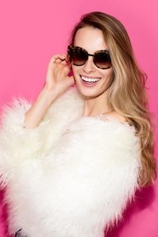 Modieuze jonge vrouw in zonnebril en een witte bontjas die op een roze achtergrond glimlacht