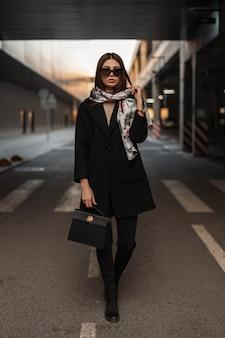Modieuze jonge vrouw in zonnebril in zijden elegante sjaal op hoofd in stijlvolle zwarte jas in jeans in laarzen met tas staat op het asfalt in de stad. business meisje model loopt op de weg op straat.