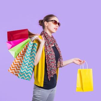 Modieuze jonge vrouw met boodschappentas over paarse achtergrond
