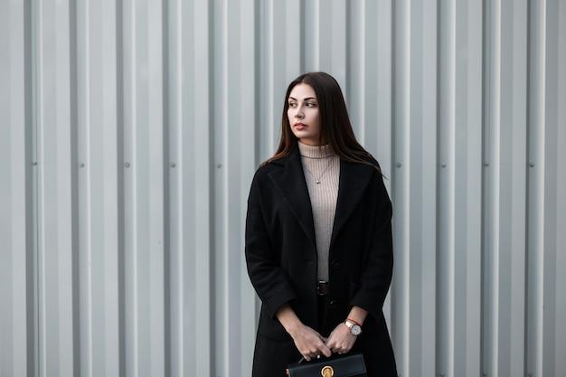 Modieuze jonge vrouw met bruin haar in zwarte modieuze jas met stijlvolle lederen zwarte handtas staat in de buurt van zilveren metalen vintage muur. moderne luxe meisje mannequin buitenshuis. trendy dame.