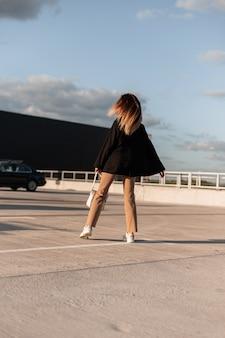 Modieuze jonge vrouw met lang bruin haar in stijlvolle vrijetijdskleding danst op een zonnige zomerdag in een buitenparkeerplaats in de stad. achteraanzicht.