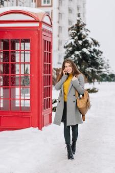 Modieuze jonge vrouw met lang donkerbruin haar, grijze jas met rugzak lopen op straat in de buurt van rode telefooncel. winterweer, sneeuwtijd, telefoneren