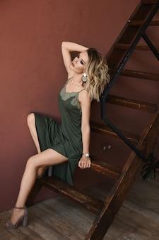 Modieuze jonge vrouw met lange sexy benen in een elegante jurk en schoenen op hoge hakken zit op houten trappen in het interieur van het huis. concept van schoonheid en mode
