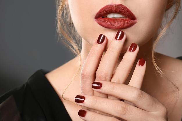 Modieuze jonge vrouw met mooie manicure op grijs, close-up