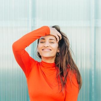 Modieuze jonge vrouw poseren tegen metalen gestreepte achtergrond