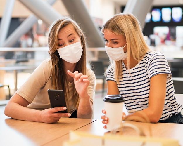 Modieuze jonge vrouwen die mobiele telefoon controleren