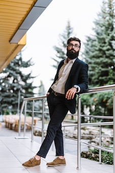 Modieuze jonge zakenman die zich dichtbij het traliewerk bevindt dat weg eruit ziet