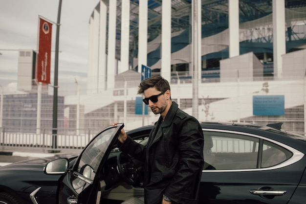 Modieuze jongeman in glazen in de buurt van de auto