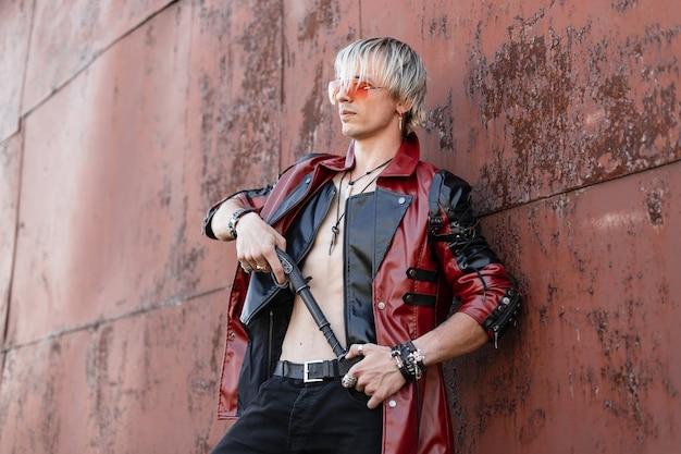 Modieuze jongeman in stijlvol zwart-rood leerjasje in trendy bril in naakte torso in een spijkerbroek met een vintage pistool vormt in de buurt van de metalen roestige muur buitenshuis.