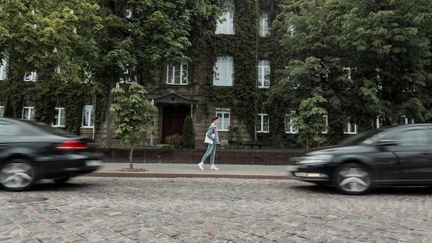 Modieuze jongeman in stijlvolle jeanskleding in sneakers met stoffen tas loopt op straat in de buurt van de weg. moderne stedelijke man reist op stad in de buurt van oud gebouw begroeid met planten.