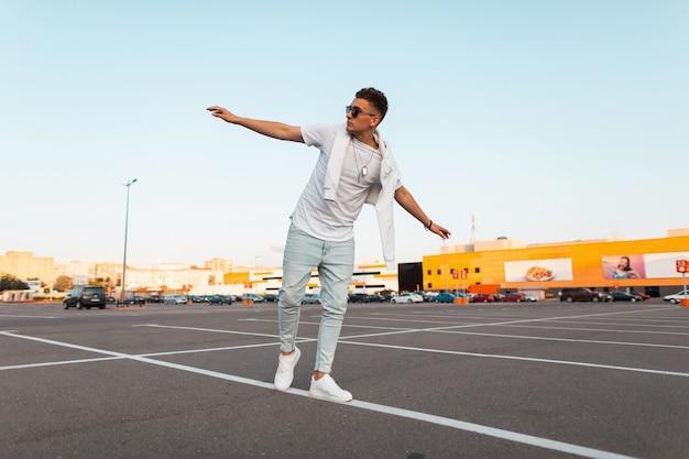 Modieuze jongeman in stijlvolle zomerkleding in vintage zonnebril in sneakers loopt op de parkeerplaats.