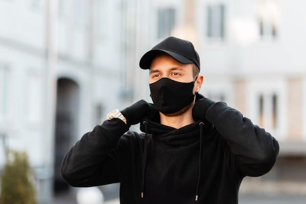 Modieuze jongeman met een beschermend medisch masker in een zwarte stijlvolle hoodie met een modepet op straat. moderne mannelijke stedelijke stijl en pandemisch concept