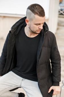 Modieuze jongeman met een kapsel in een stijlvolle zwarte winterjas zit op straat