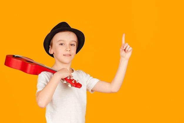 Modieuze jongen in zomer hoed geïsoleerd over oranje achtergrond. kleine jongen speelt op hawaiiaanse gitaar en heeft plezier. gelukkig kind genieten van de muziek.