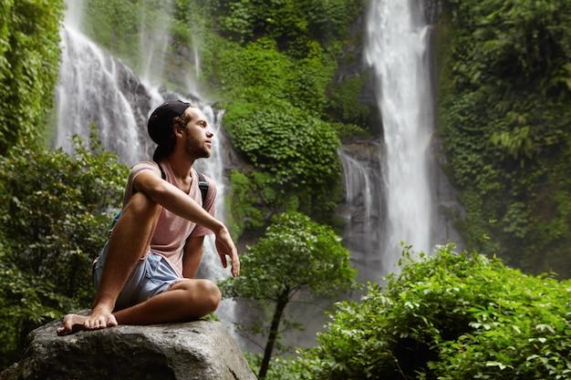 Modieuze kaukasische wandelaar gekleed terloops zittend blootsvoets op grote steen en ontspannen tijdens zware en lange reis in het regenwoud. bebaarde man in snapback overweegt prachtige natuur om hem heen