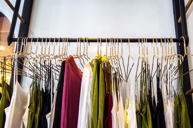 Modieuze kleding hangt in de winkel