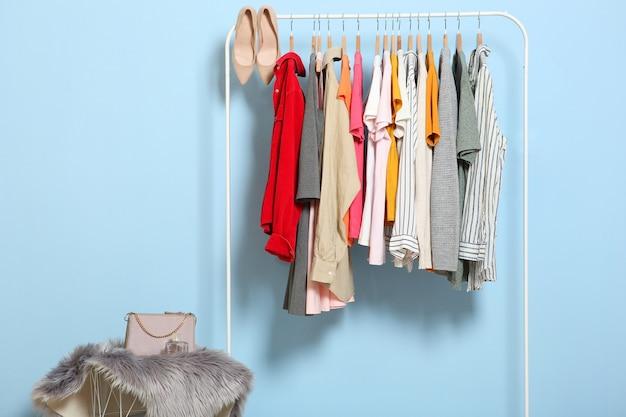 Modieuze kleding op hangers op een garderoberek op een gekleurde achtergrond
