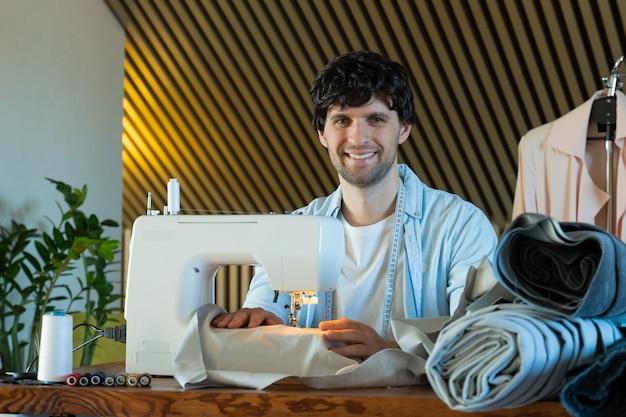 Modieuze kledingontwerper man naait bij een naaimachine modeontwerper die in zijn atelier werkt