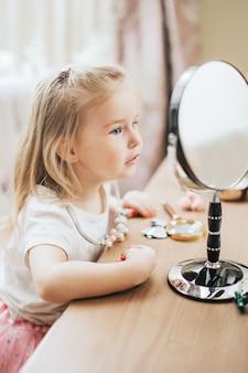 Modieuze kleine dame die haar haar kamt en in de spiegel kijkt