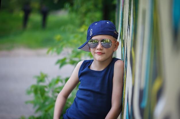 Modieuze kleine jongen in zonnebril en cap. graffiti achtergrond. childhood. summertime.