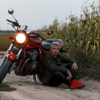 Modieuze knappe brutale man in een kaki jas zit in de buurt van een motorfiets in het veld