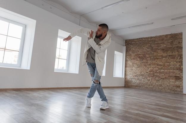 Modieuze knappe jonge danseres man in een stijlvol jasje met een capuchon en gescheurde spijkerbroek dansen in een dansstudio
