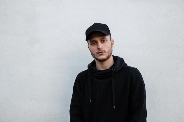 Modieuze knappe jonge hipster man in stijlvolle zwarte mock-up pet met hoodie staat in de buurt van grijze muur op straat