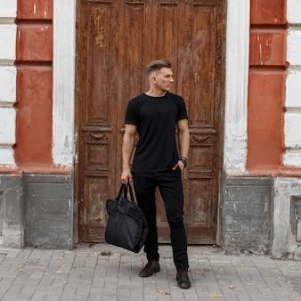 Modieuze knappe jonge stijlvolle model man met kapsel in zwarte mockup kleding met mode zwarte tas in de buurt van een vintage houten deur