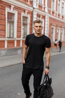 Modieuze knappe jonge stijlvolle model man met kapsel in zwarte stijlvolle kleding met een zwarte tas loopt op straat in de stad