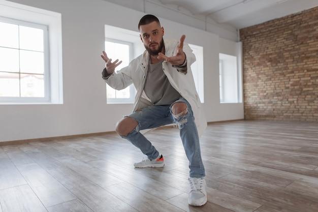 Modieuze knappe jongeman danser in stijlvolle kleding met gescheurde spijkerbroek dansen in dansles