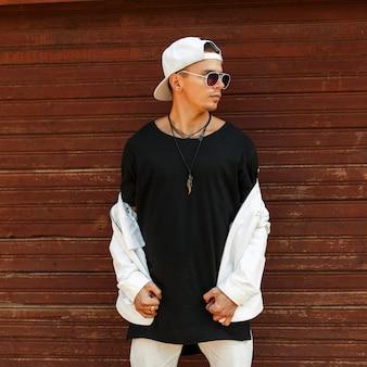 Modieuze knappe man in een zwart t-shirt met een witte baseballpet en zonnebril poseren in de buurt van een houten muur