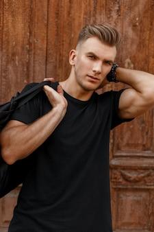 Modieuze knappe man met een kapsel in een zwart t-shirt met een zwarte tas staat bij de vintage houten deur
