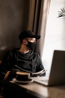 Modieuze knappe man met een medisch beschermend masker en een zwarte pet in een stijlvolle hoodie met een laptop en koffie leest een tijdschrift in een café