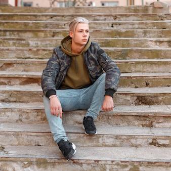 Modieuze knappe man met haar in een militair jasje met spijkerbroek en sneakers zittend op de trap