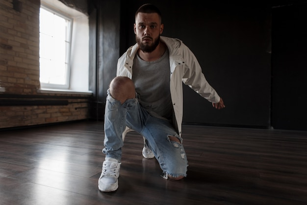 Modieuze knappe model man met een baard in een wit jasje met blauwe gescheurde spijkerbroek met sneakers poseren in een donkere studioruimte