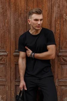 Modieuze knappe model man met kapsel in zwart t-shirt staat in de buurt van een houten vintage muur