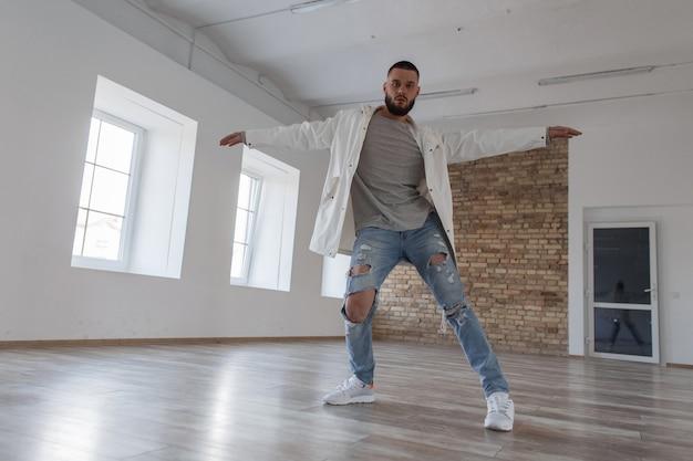 Modieuze knappe stijlvolle jongeman danser in jasje en gescheurde spijkerbroek dansen in dansstudio