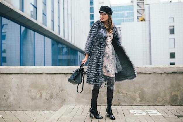 Modieuze lachende vrouw wandelen in de stad in warme bontjas, winterseizoen, koud weer, zwarte pet, jurk, laarzen, lederen tas, straat modetrend dragen