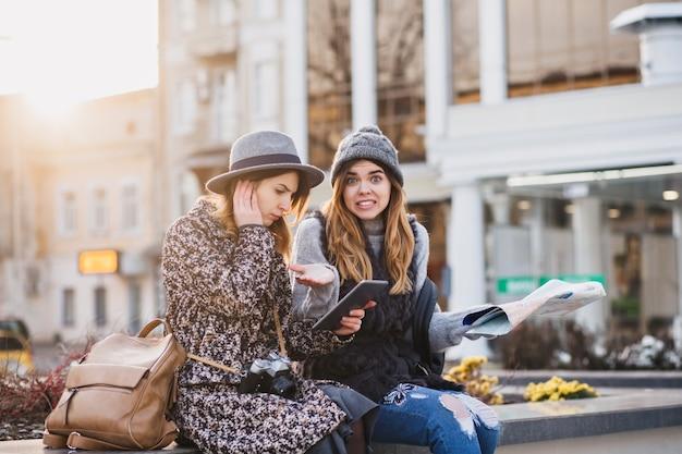 Modieuze lachende vrouwen die in het centrum van de stad zitten en heldere emoties uitdrukken op een zonnige dag in de stad. gelukkig samen reizen, proberen de locatie op de kaart te vinden.