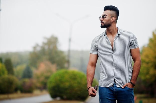 Modieuze lange bebaarde man met overhemd, spijkerbroek en zonnebril gesteld op park en portemonnee bij de hand houden