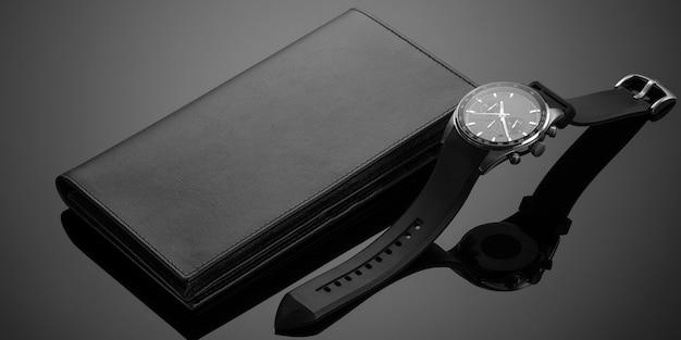 Modieuze leren herenportemonnee en horloge op een zwarte achtergrond