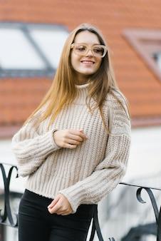 Modieuze levensstijl portret van een jonge glimlachende vrouw gekleed in een gebreide trui en glazen