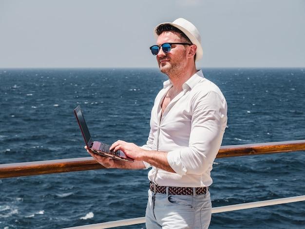 Modieuze man aan het werk op een rode laptop